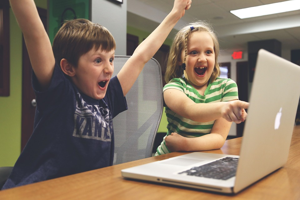 Børn råber af glæde foran computer